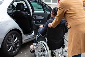 Man With Her Disabled Wife Moving Towards Car