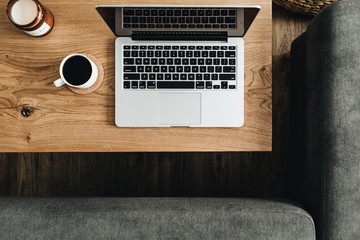 Laptop, coffee cup on wooden table. Flat lay, top view blogger / freelancer workspace minimal concept.