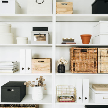 Modern home office cabinet interior design concept. White storage shelves with boxes, eucalyptus, decorations. Scandinavian style room.