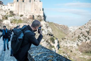Giovane ragazzo che fotografa il panorama con il cellulare a Matera sul bordo di un belvedere con cielo azzurro