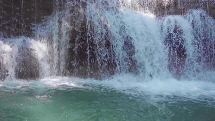 Wall Mural - Slow motion of Erawan waterfall in Kanchanaburi, Thailand. Beautiful waterfall with emerald pool in nature.