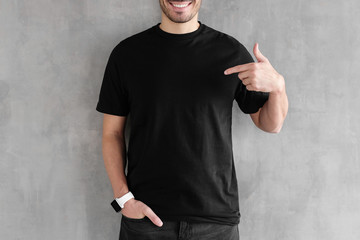 Young man isolated on gray textured wall, smiling while pointing with index finger to black t-shirt, copyspace for advertising Wall mural