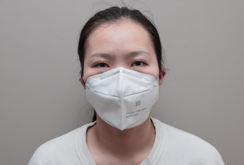 Portrait of Asian woman using N95 respirator mask for protecting air pollution