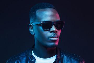 Obraz Neon studio portrait of african american male model wearing trendy sunglasses and leather jacket - fototapety do salonu