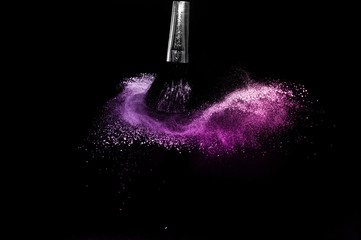 Cosmetic brush with purple cosmetic powder spreading for makeup artist and graphic design in black background