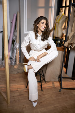 Fashion designer in light clothes in sewing workshop