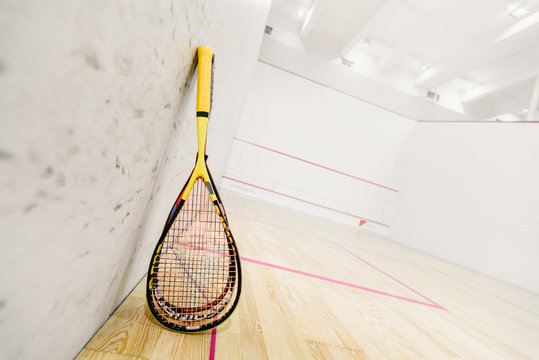 Closeup photo of squash rackets on empty squash court