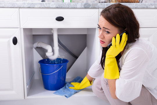 Woman Calling Plumber In Front Of Water Leaking From Pipe