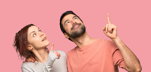 Couple in valentine day pointing up with the index over isolated pink background Wall mural