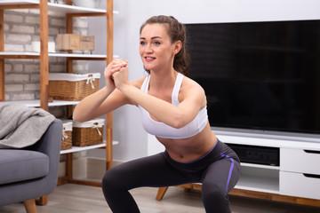Happy Woman Doing Squat Exercise
