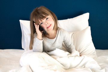 girl talking on phone in bed
