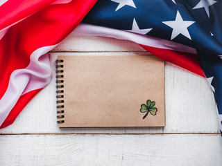 Notepad with congratulatory inscription and american star striped flag. St.Patrick's Day. Beautiful card. Close-up, wooden surface. Congratulations for loved ones, relatives, friends and colleagues