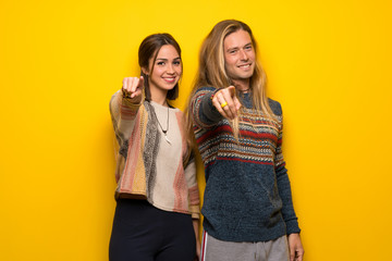 Hippie couple over yellow background points finger at you with a confident expression