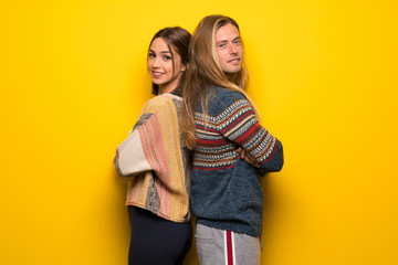 Hippie couple over yellow background in lateral position