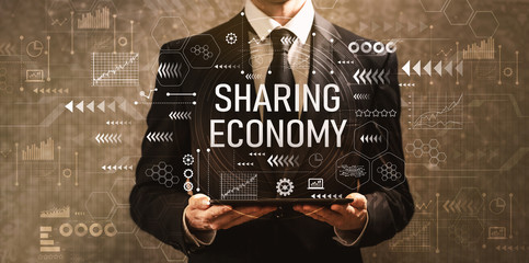 Sharing economy with businessman holding a tablet computer on a dark vintage background