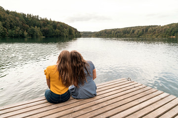 Close women on pier in picturesque nature