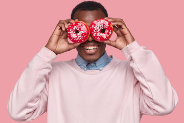 Positive dark skinned man covers eyes with glazed tasty donuts, has sweet obsession, breaks diet, wears casual sweatshirt, smiles broadly, isolated over pink background, feels hungry for doughnuts