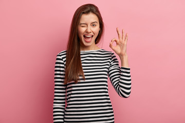 Photo of cheerful young woman blinks eye, makes okay gesture, demonstrates her agreement, feels happy, wears black and white striped jumper, isolated over pink background. Body language concept Wall mural