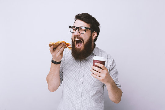 Happy hungry bearded man eating a slice of pizza and hold his cup of coffee