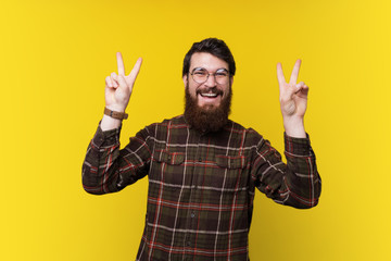Portrait of handsome bearded guy gesturing peace, victory  symbol over yellow background