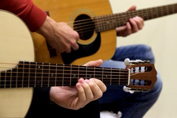 "Closeup at left hand of guitarist learning how to play acoustic guitar instrument of traditional Greek music of ""rempetika"" as also jazz blues rock and roll from teacher maestro at the background"