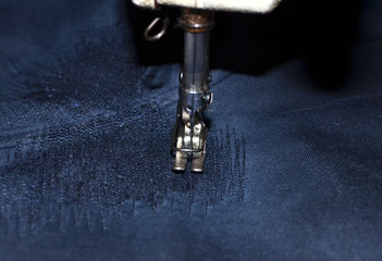 Stitching, stitch a hole in dark blue jeans or knit sweatpants with a sewing machine. Part of the sewing machine and denim closeup. Tailoring