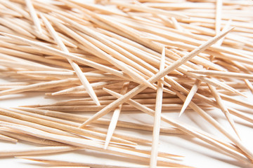 A bunch of unused round toothpicks from light-colored wood arrayed on a white plain background. Fotoväggar