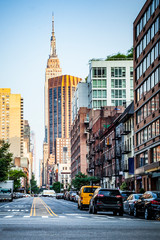34nd street, Manhattan viewed from Hudson River pedestrian zone with Empire State Building in background in New York City during sunny summer daytime at sunset