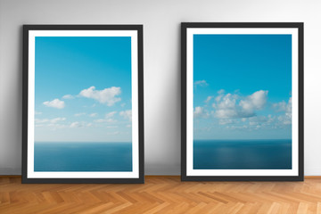 framed picture prints of ocean and blue sky landscape photography on wooden floor  -