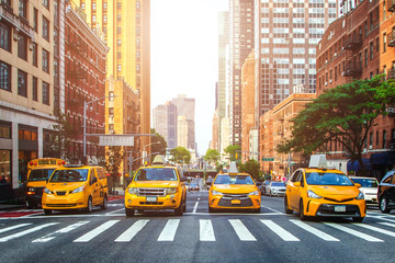 Yellow cabs waiting for green light on the crossroad of streets of New York City during sunny...