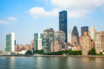 View of Midtown Manhattan skyline and the United Nations headquarters, viewed from Roosevelt Island over the East River during sunny summer day