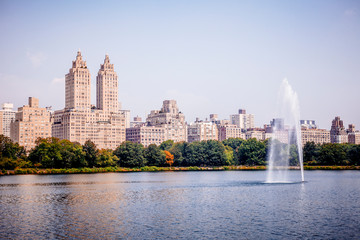 View of Manhattan skyline viewed from Jacqueline Kennedy Onassis Reservoir in Central Park in New York City during sunny summer day