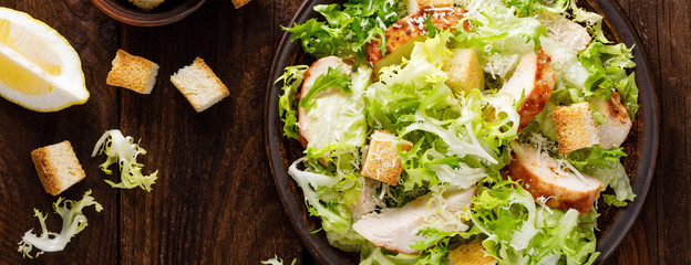 Caesar salad with grilled chicken meat, fresh lettuce, parmesan cheese and fried croutons. Classic North American cuisine. Top view. Banner