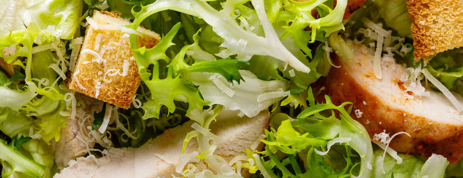 Caesar salad with grilled chicken meat, fresh lettuce, parmesan cheese and fried croutons. Classic North American cuisine. Top view. Background. Banner