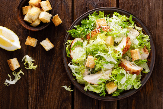 Caesar salad with grilled chicken meat, fresh lettuce, parmesan cheese and fried croutons. Classic North American cuisine. Top view