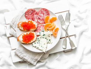 Breakfast in bed - red caviar sandwiches, blue cheese, salami, tangerines on a light background, top view. Flat lay, copy space