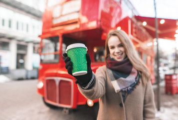 Smiling girl standing in the street in warm clothes holds a paper glass with coffee at the background of the bus cafe. Lady in the coat holds a cup of coffee. Focus on a paper cup.