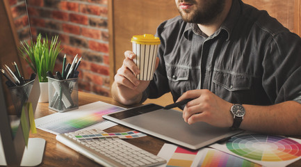 Young creative artist of web design in hat with graphic tablet in modern loft office