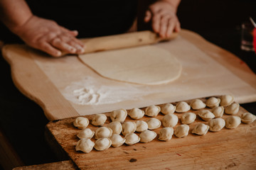 Uncooked russian pelmeni on cutting board and ingredients for homemade pelmeni on white table. Process of making pelmeni, ravioli or dumplings with meat