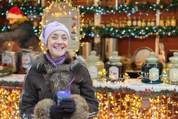 Beautiful young woman with coffee cup in the city. Beautiful woman with coffee on the street in winter clothes. Woman Having Hot Drink Outdoors On Winter Market.
