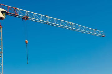 construction tower crane against blue sky. close up