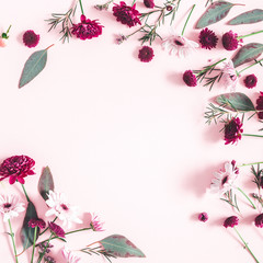 Flowers composition. Eucalyptus leaves and pink flowers on pastel pink background. Flat lay, top view, copy space, square