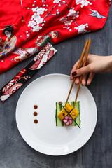 Hand with chopstiks taking a piece of tamagoyaki