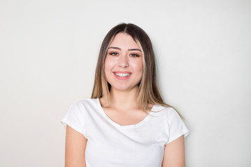 Portrait of young beautiful cute cheerful girl smiling looking at camera over white background.
