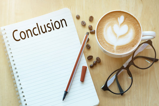 Conclusion word on notebook with glasses, pencil and coffee cup on wooden table. Business concept.