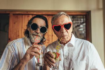 Retired men wearing funny sunglasses drinking juice