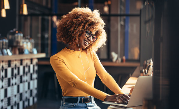 Smiling woman on a video call sitting at a coffee shop