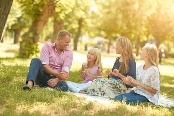 Happy family with smiles picnic in the park on a sunny day Wall mural