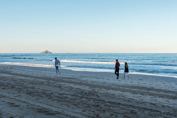 Photographer and clients go along the sea to choose a place for a photo shoot. La Manga. Spain.