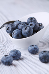 Ripe and sweet blueberries on a textured wooden table in a beautiful white ceramic Cup